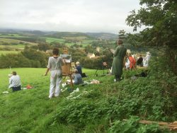 several artists painting outside in the dorset countryside